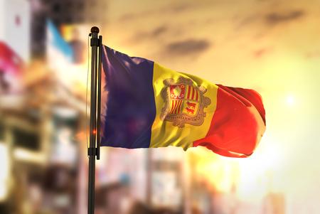 Andorra Flag Against City Blurred Background At Sunrise Backlight