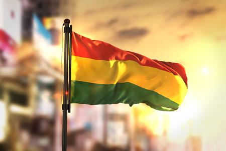 Bandera de Bolivia contra la ciudad Fondo borrosa al contraluz de la salida del sol Foto de archivo