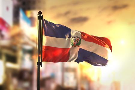 市に対してドミニカ共和国の国旗がぼやけて日の出バックライトで背景 写真素材