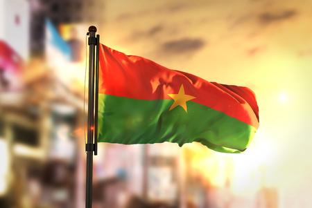 Burkina Faso Flag Against City Blurred Background At Sunrise Backlight Stock Photo