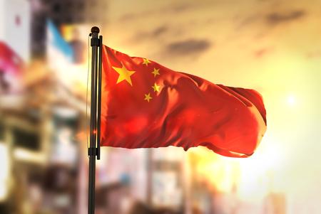 De Vlag van China tegen Stad Vage Achtergrond bij Zonsopgang Backlight