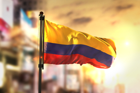 都市に対してコロンビアの国旗日の出バックライトで背景がぼやけ
