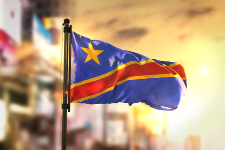 Democratic Republic of the Congo Flag Against City Blurred Background At Sunrise Backlight Stock Photo