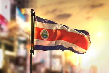 Costa Rica Flag Against City Blurred Background At Sunrise Backlight Фото со стока