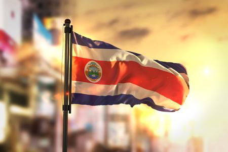 Costa Rica Flag Against City Blurred Background At Sunrise Backlight Stok Fotoğraf