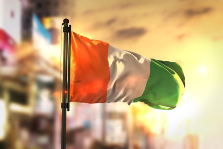Ivory Coast Flag Against City Blurred Background At Sunrise Backlight Stock Photo