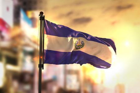 El Salvador Flag Against City Blurred Background At Sunrise Backlight Stock Photo