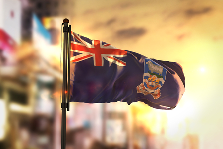 Falkland Islands Flag Against City Blurred Background At Sunrise Backlight