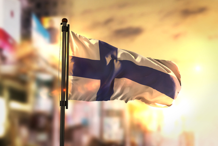 Finland Flag Against City Blurred Background At Sunrise Backlight