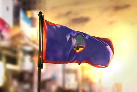 Guam Flag Against City Blurred Background At Sunrise Backlight