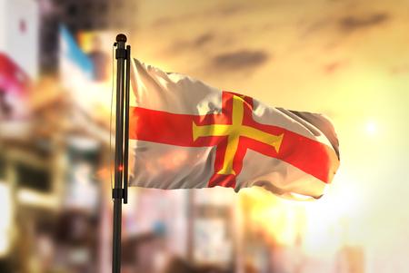 Guernsey Flag Against City Blurred Background At Sunrise Backlight
