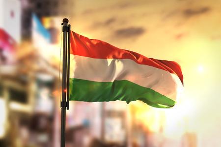Hungary Flag Against City Blurred Background At Sunrise Backlight Stock Photo