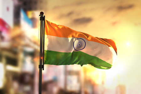 India Flag Against City Blurred Background At Sunrise Backlight Stock Photo