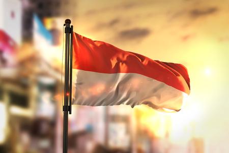 都市に対してインドネシアの国旗日の出バックライトで背景がぼやけ 写真素材