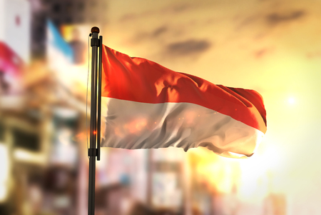 Indonesia Flag Against City Blurred Background At Sunrise Backlight
