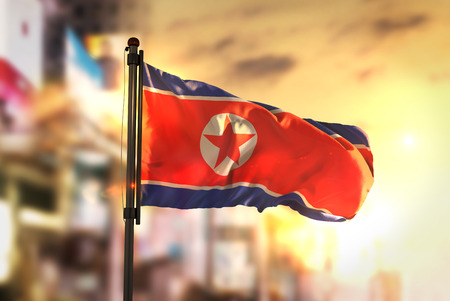 North Korea Flag Against City Blurred Background At Sunrise Backlight