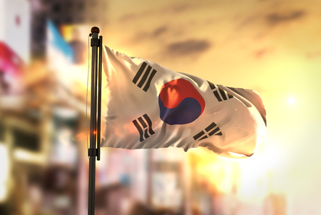 republic of korea: South Korea Flag Against City Blurred Background At Sunrise Backlight