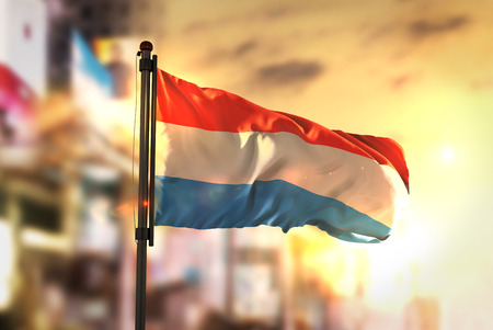 Luxembourg Flag Against City Blurred Background At Sunrise Backlight