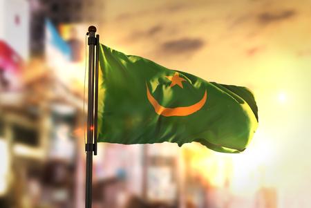 Mauritania Flag Against City Blurred Background At Sunrise Backlight Stock Photo