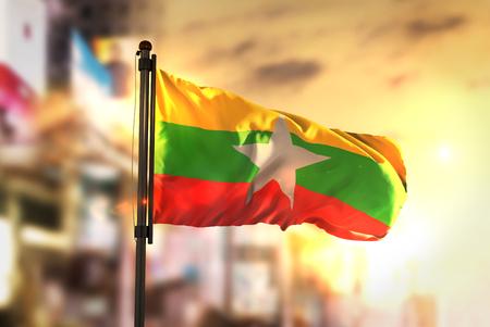 市に対するミャンマーの国旗日の出バックライトで背景がぼやけてください。 写真素材