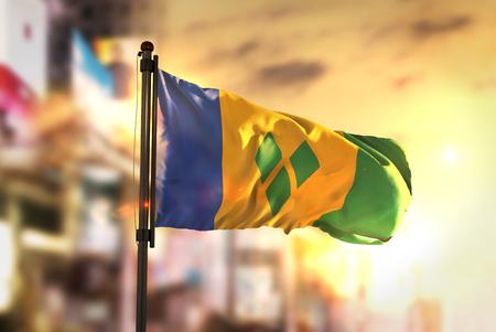 Saint Vincent and the Grenadines Flag Against City Blurred Background At Sunrise Backlight