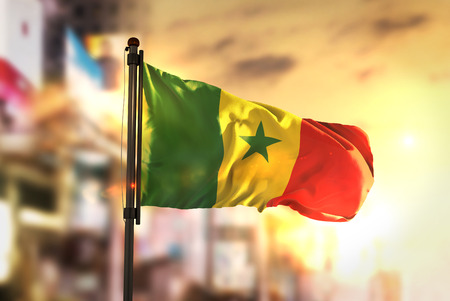 Senegal Flag Against City Blurred Background At Sunrise Backlight Stock Photo