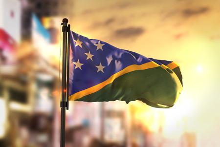Solomon Islands Flag Against City Blurred Background At Sunrise Backlight Stock Photo