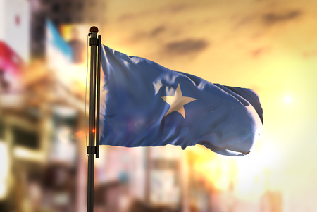 Somalia Flag Against City Blurred Background At Sunrise Backlight