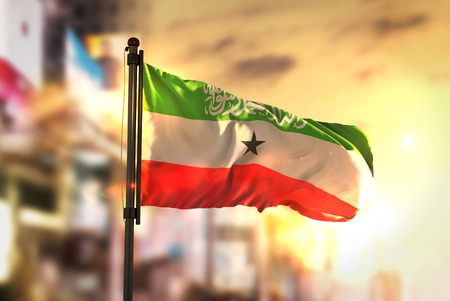 Somaliland Flag Against City Blurred Background At Sunrise Backlight Stock Photo