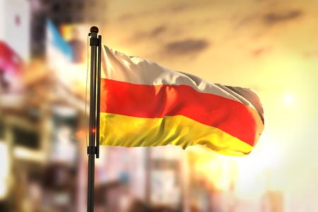South Ossetia Flag Against City Blurred Background At Sunrise Backlight