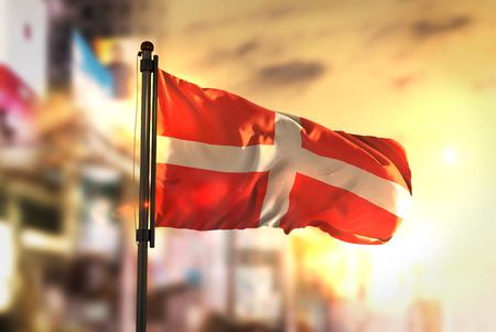 Sovereign Military Order of Malta Flag Against City Blurred Background At Sunrise Backlight
