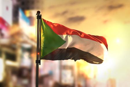 Sudan Flag Against City Blurred Background At Sunrise Backlight
