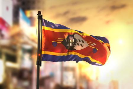 Swaziland Flag Against City Blurred Background At Sunrise Backlight Stock Photo