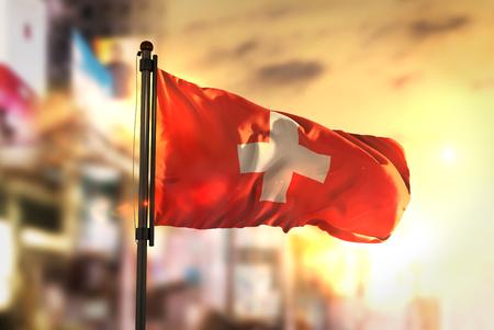 Switzerland Flag Against City Blurred Background At Sunrise Backlight Stock Photo