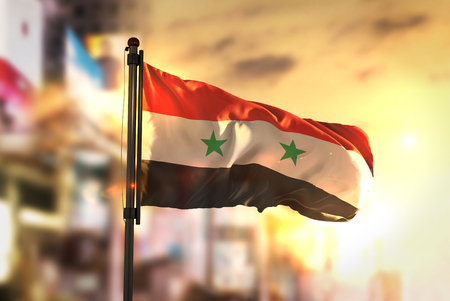 Syria Flag Against City Blurred Background At Sunrise Backlight