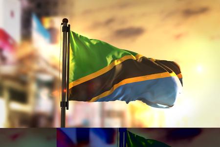 Tanzania Flag Against City Blurred Background At Sunrise Backlight Stock Photo