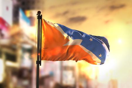 Tierra del Fuego Flag Against City Blurred Background At Sunrise Backlight