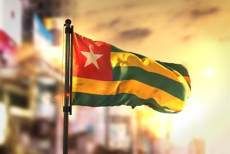 Togo vlajka proti městu rozmazané pozadí na východ slunce podsvícení
