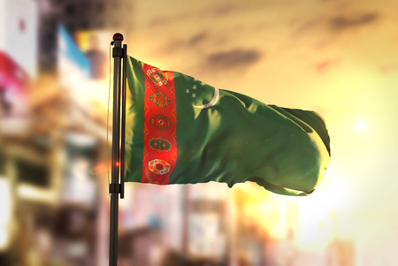 Turkmenistan Flag Against City Blurred Background At Sunrise Backlight