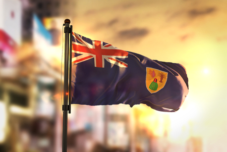 Turks and Caicos Islands Flag Against City Blurred Background At Sunrise Backlight