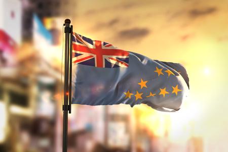 Tuvalu Flag Against City Blurred Background At Sunrise Backlight Stock Photo