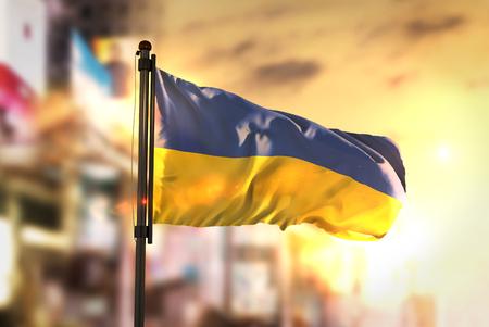 Ukraine Flag Against City Blurred Background At Sunrise Backlight