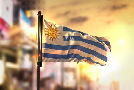 Uruguay Flag Against City Blurred Background At Sunrise Backlight