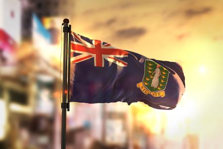 British Virgin Islands Flag Against City Blurred Background At Sunrise Backlight Stock Photo