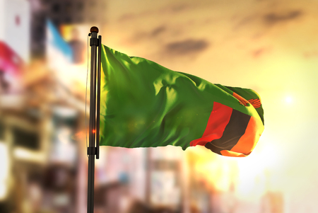 Zambia Flag Against City Blurred Background At Sunrise Backlight