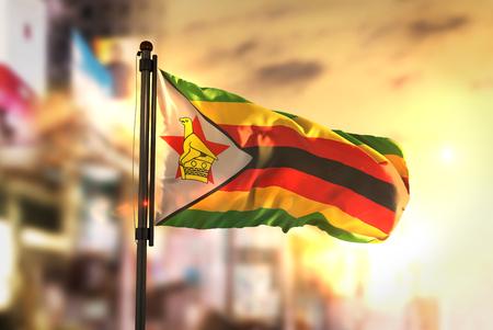 Zimbabwe Flag Against City Blurred Background At Sunrise Backlight