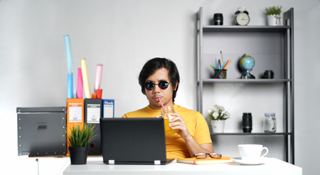 Young Man Working With Laptop and Drinking Orange Juice on Summer Vacation Season at Office
