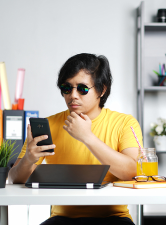 Young Man Checking Smartphone on Summer Vacation Season at Office