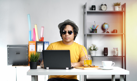 Young Man Working With Laptop Wearing Fedora Hat on Summer Vacation Season at Office