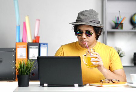 Young Man Working With Laptop and Drinking Orange Juice Wearing Fedora Hat on Summer Vacation Season at Office